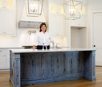 Woman standing at an island in kitchen